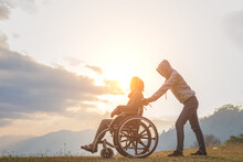 Disabled Handicapped Woman In Wheelchair And Care Helper Walking On Mountain Sunset.