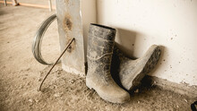 A Dirty Pair Of Rubber Boots Full Of Dried Concrete Lies On The Unfinished Bare Floor Of A Building Under Construction.