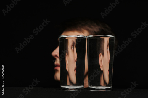 Foto strange portrait of a man in profile through two glasses of water