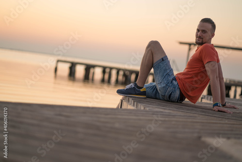 Man Sitting On Pier Over Sea Against Sky During Sunset
