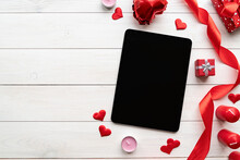 Tablet With Black Screen With Valentine Decorations Candles, Balloons And Confetti Top View On White Wooden Background