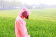 Woman In Raincoat Standing Against Field