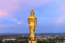 Golden Walking Buddha Statue On Hill Or Mountain To At Wat Phrathat Khao Noi Temple During Twilight, Nan Province, Thailand