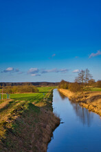 Narrow River Flowing Through The Fields Under The Blue Clear Sky