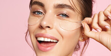 Close Up Of Caucasian Girl With Natural No Makeup Look And White Smile, Take Off Silicone Under Eye Patches And Smiling Happy, Using Skincare Products From Dark Circles, Pink Background