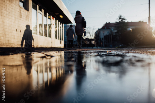 Fototapeta Rear View Of People Walking On Puddle On Footpath In City Against Sky