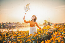 Woman Holding Pinwheel Toy While Standing By Flowering Plants Against Sky During Sunset