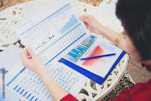 Tableau sur Toile Cropped Hand Of Businesswoman Holding Document While Sitting At Table