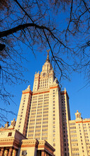 Sunny Main Building Of Moscow University Through Naked Tree Branches Under Blue Sky