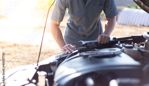 Midsection Of Mechanic Examining Breakdown Car On Road Fototapet