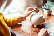 Cropped Image Of Woman Inserting Money In Piggy Bank On Table At Home