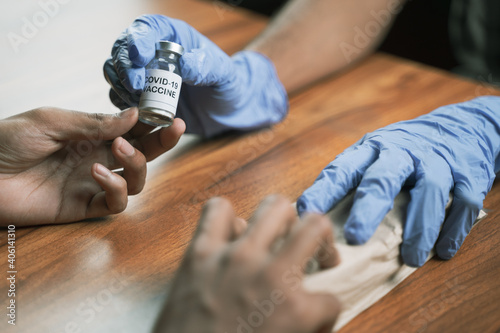 Obraz Doctor selling covid-19 vaccine bottle for the money at hospital - Concept of Covid-19 coronavirus vaccination bribery and corruption. - fototapety do salonu