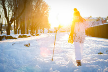 Teenage Girl Running In The Snow With Mountain Cane