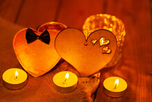 Two Hearts And Candles On Wooden Boards. St Valentine's Day Greeting Card With Candles And Hearts On A Blurred Background. Love Story Concept