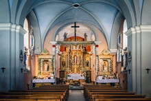 Inside A Small Christian Church With Wooden Cross, Golden Altar And Statues Of Saints