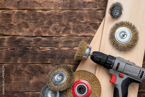 Fototapeta Cordless screwdriver with grinding disc and wooden bars on the wooden workbench background with copy space. obraz