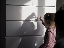 Side View Of Girl Standing Against Wall