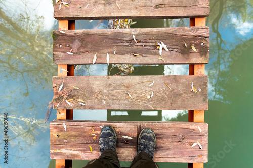 pies que empiezan a cruzar un puente de madera sobre un rio