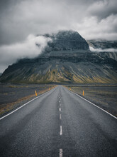 Vertical Shot Of An Empty Road With Rocky Mountains And The Fog In The Background
