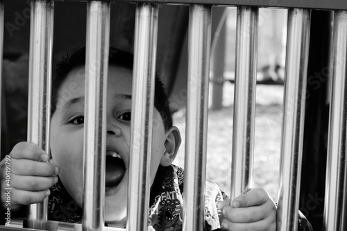 Carta da parati Close-up Portrait Of Boy Screaming Through Window