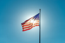 American Flag Against A Clear Blue Sky Lit From Behind By The Sun