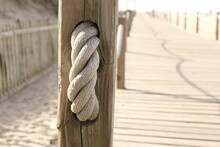 Close-up Of Rope Tied To Wooden Post.