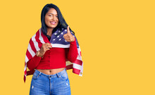 Hispanic Woman With Long Hair Holding United States Flag Smiling Happy And Positive, Thumb Up Doing Excellent And Approval Sign