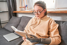 Woman With Artificial Limb Reading Storybook Attentively