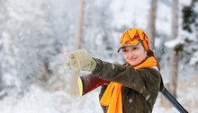 A Young Beautiful Hunter Woman On Hunt In Forest With Rifle On The Shoulder. Winter Season. In The Background Are Snowy Trees. Copy Space For Text.