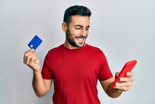 Young Hispanic Man Holding Smartphone And Credit Card Smiling With A Happy And Cool Smile On Face. Showing Teeth.