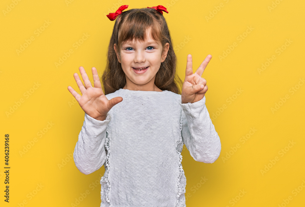 Fototapeta Little caucasian girl kid wearing casual clothes showing and pointing up with fingers number seven while smiling confident and happy.
