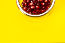 Pomegranate Seeds In A Glass Jar On A Yellow Background