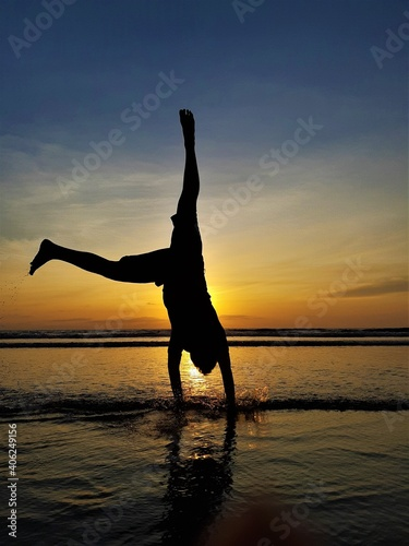 Fotografie, Obraz Silhouette Man With Arms Raised On Beach Against Sky During Sunset