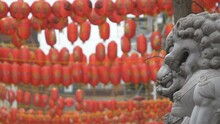 Chinese Paper Lanterns Behind A Sculpture Of Lions.