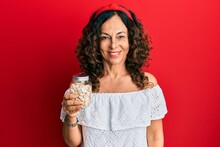 Middle Age Hispanic Woman Holding Jar With Pumpkin Seeds Looking Positive And Happy Standing And Smiling With A Confident Smile Showing Teeth