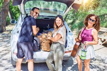 Family Smiling Happy Looking At The Camera. Holding Suitcase And Backpack To The Car Trunk At Forest