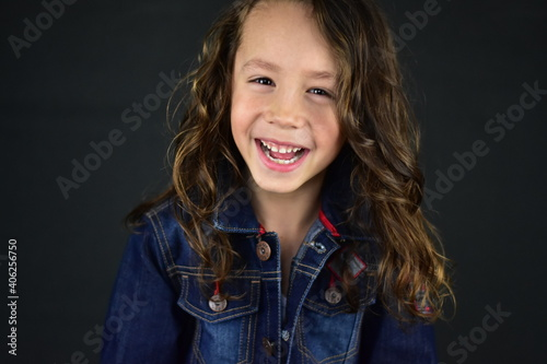 Fototapeta premium Portrait Of Smiling Girl Against Black Background