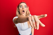 Young Caucasian Woman Wearing Casual White T Shirt Pointing With Finger Surprised Ahead, Open Mouth Amazed Expression, Something On The Front