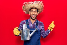 Young Latin Man Wearing Farmer Hat And Gloves Holding Watering Can Pointing Thumb Up To The Side Smiling Happy With Open Mouth