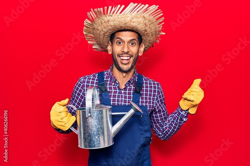 Obraz Young latin man wearing farmer hat and gloves holding watering can pointing thumb up to the side smiling happy with open mouth - fototapety do salonu