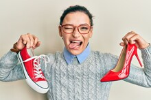 Young Caucasian Woman Choosing High Heel Shoes And Sneakers Sticking Tongue Out Happy With Funny Expression.