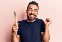 Young Hispanic Man Holding Paintbrushes Screaming Proud, Celebrating Victory And Success Very Excited With Raised Arm