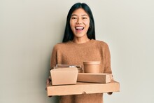 Young Chinese Woman Holding Take Away Food Smiling And Laughing Hard Out Loud Because Funny Crazy Joke.