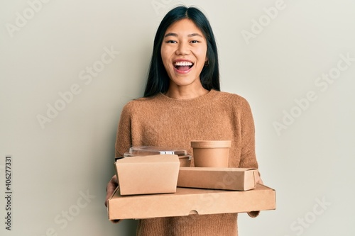 Obraz na plátně Young chinese woman holding take away food smiling and laughing hard out loud because funny crazy joke