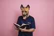 Young man in a latex dog head mask taking some notes on a pink background