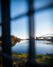 Views Of Water, Boathouse, And Bridge Through A Fence