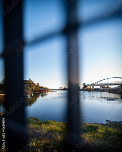 Canvas Views of water, boathouse, and bridge through a fence