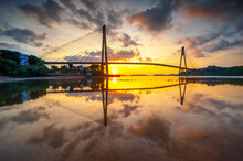 Reflection Of Bridge On Water Against Orange Sky