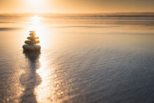 Beach Sunset And Stones Balance, Soft Yellow-pink Sunlight With Beautiful Sun Reflections On Golden Sand