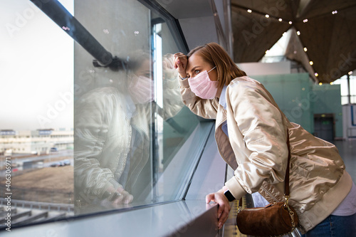 Fotografía Side View Of Woman Wearing Mask Looking Through Window At Airport